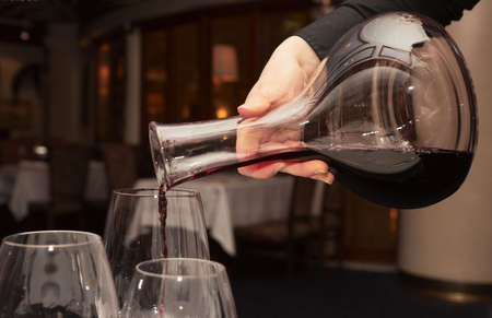 decanter: Waiter pouring red wine from decanter in dark restaurant
