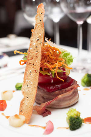 Elegant tenderloin steak with steamed vegetables topped with deep fried onion, tomato and herbs