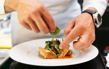 Chef is decorating delicious dish, motion blur on hands Stock Photo