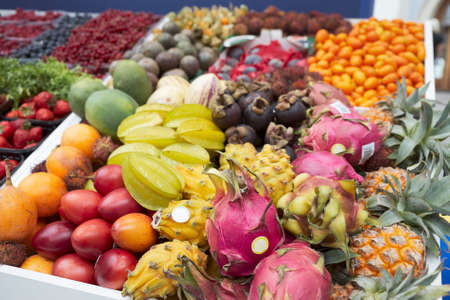 Various trropical fruits and berries lying on market stall photo