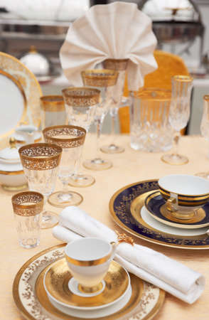 Set of fine bone porcelain dishware and crystal, shallow focus photo