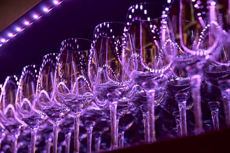 Rows of wineglasses illuminated with blue lamps photo