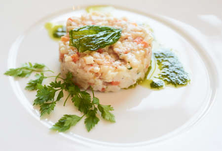 tartare: Elegant seabass tartare with parsley and pesto topped with fried basil leaf