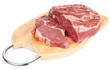Piece of ribeye on cutting plank isolated with soft shadow photo