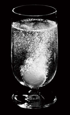reaction: Medical pill dissolving in water, monochrome, isolated on black