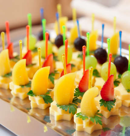 banquet table: Canapes of cheese with fruits, close-up shot