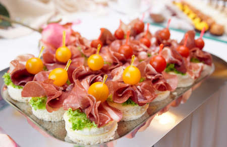 food buffet: Canapes with cured ham (jamon or prosciutto) on banquet table