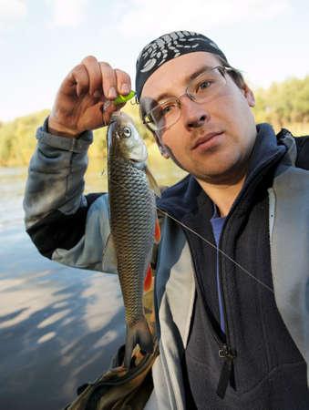 Fisherman holds chub caught on a green hardbait Stock Photo - 8003513