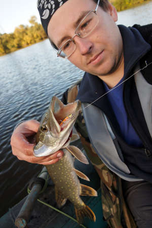 Fisherman holding northern pike with hardbait in its mouth Stock Photo - 8003516