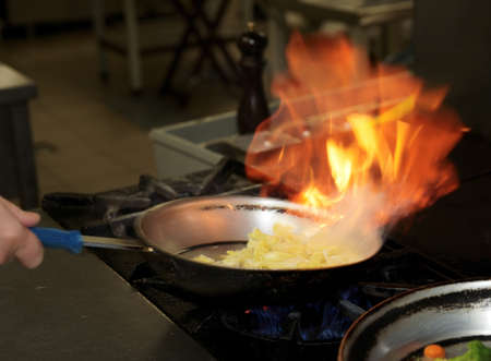 pan fried: Chef is making flambe sauce on restaurant kitchen Stock Photo