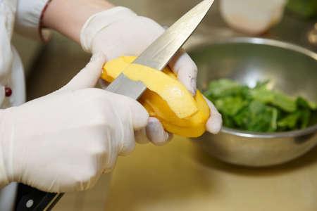 Chef-kok is peeling mango voor een aperitief