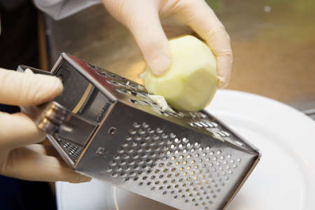 Chef is zesting apple with metal shredder, slight motion blur photo