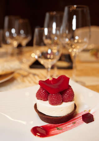 Dessert on plate in restaurant with wineglasses in blurred  background photo