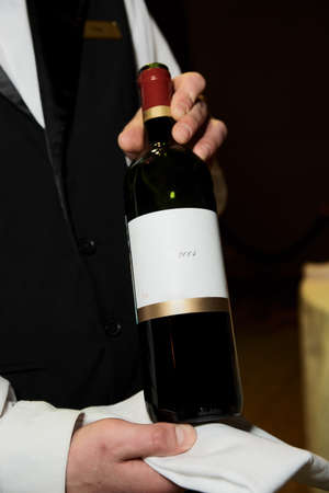 hospitality staff: Sommelier displaying wine during formal dinner, TMs removed from the bottle