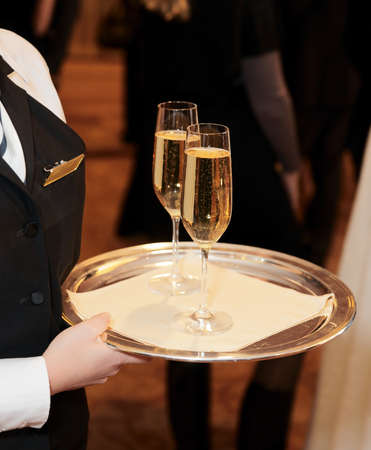 Female waiter welcomes guests with champagne photo