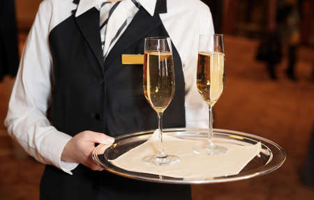 Female waiter welcomes guests with champagne
