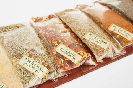 Set of greek spices on wooden plank, light gray background photo