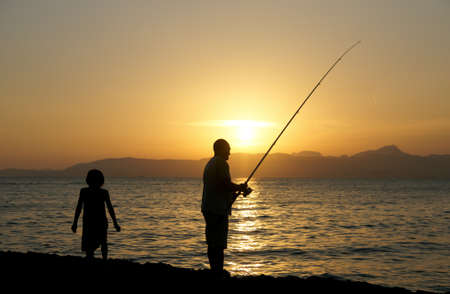 Man and a little girl fishing in the evening, Mallorca, Spain photo