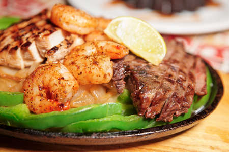 american cuisine: Fajitas in metal pan on wooden plank, shallow focus Stock Photo