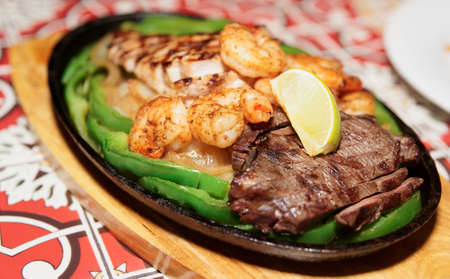 Fajitas in metal pan on wooden plank, shallow focus photo