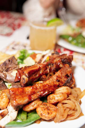 Grilled pork ribs and shrimps with coctail - perfect dinner photo