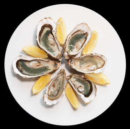 baclground: Fresh oysters on plate with lemon isolated on black baclground