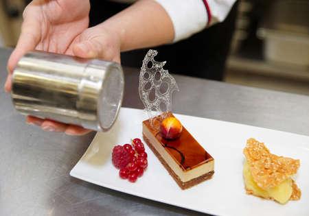 decoracion de pasteles: Pastelero profesional es decorar un postre con polvo de az�car Foto de archivo
