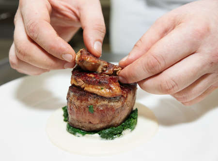 Chef is topping tenderloin steak with fried foie gras pieces photo