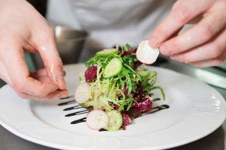 comida gourment: Cocinero es decorar aperitivo con mezcla de lechuga