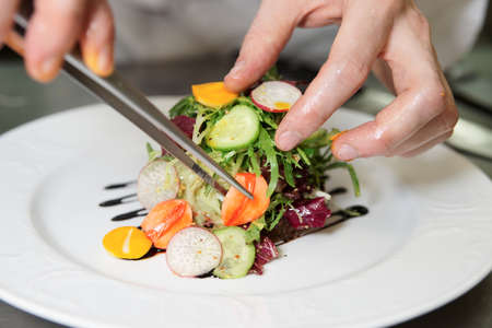 preparing: Chef is precisely decorating a dish with pincers Stock Photo