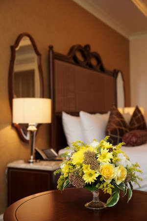 Hotel bedroom arranged with bunch of yellow flowers photo