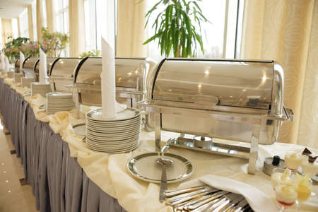 wedding table setting: Table with dishware and shiny marmites waiting for guests