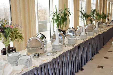 Table with dishware and shiny marmites waiting for guests photo