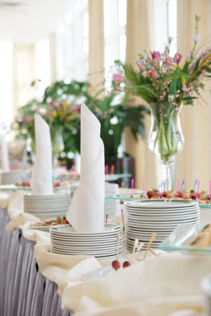 Table with dishware and tasty food waiting for guests photo