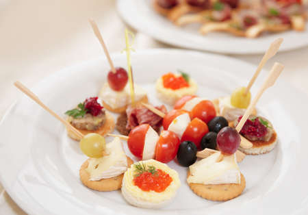 Canapes with cheese, ham and fruits on porcelain plate photo