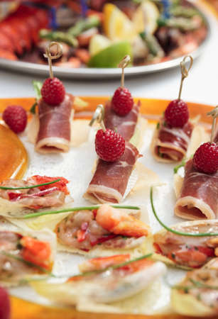 cured: Rolls with cured ham (jamon or prosciutto) on banquet table  Stock Photo