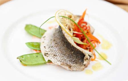 Seabass haute cuisine dish with various vegetables photo