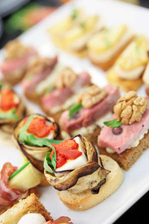 Various snacks in plate on banquet table photo