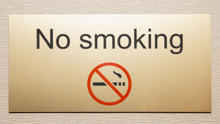 restricting: Shiny brass plate restricting smoking on hotel floor