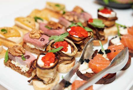 mesa para banquetes: Varios bocadillos en placa en mesa de banquete Foto de archivo