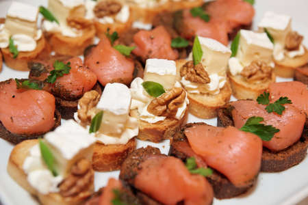 tapas: Various snacks with soft cheese and salmon in plate on banquet table Stock Photo