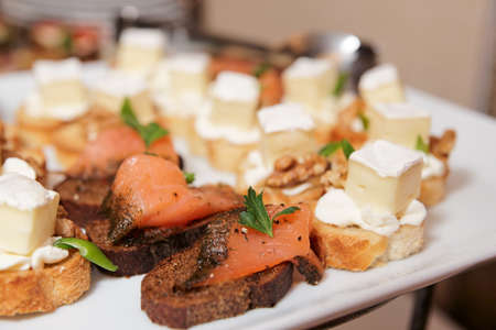 Various snacks with soft cheese and salmon in plate on banquet table Stock Photo