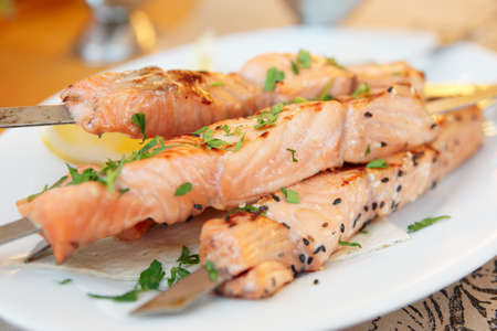 Grilled salmon on metal sticks on porcelain plate  photo