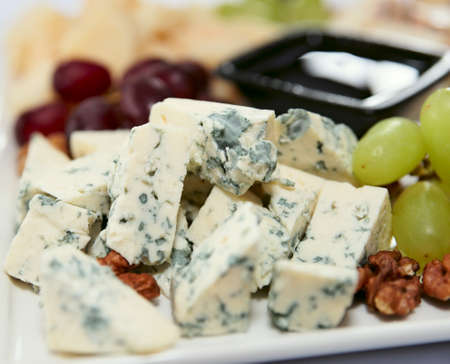 Blue cheese with grapes and nuts, macro shot, mould is seen in details