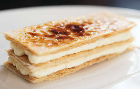Slice of mille-feuille cake on porcelain plate Stock Photo