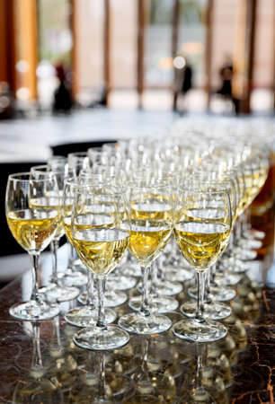 Glasses of white wine on bar counter, selective focus photo