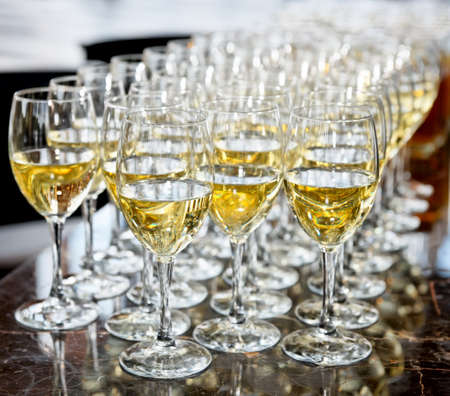 Glasses of white wine on bar counter, selective focus