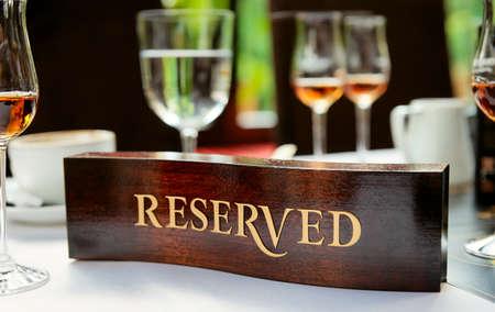 Houten voorbehouden plaat op een gearrangeerd restaurant tafel
