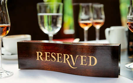 reserved sign: Wooden reserved plate on an arranged restaurant table
