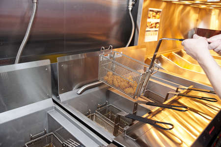 fryer: Deep fryer with boiling oil on restaurant kitchen